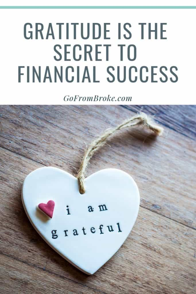 Pinterest image with text phrase Gratitude is the Secret to Financial Success and a picture of a heart charm with the words I am grateful etched on it.