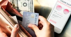 Hand pulling credit card from wallet to complete online shopping purchase from cell phone
