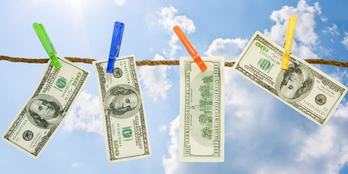 Spring cleaning your finances image shows hundred dollar bills drying on a clothesline with a bright blue sunny sky as a backdrop.