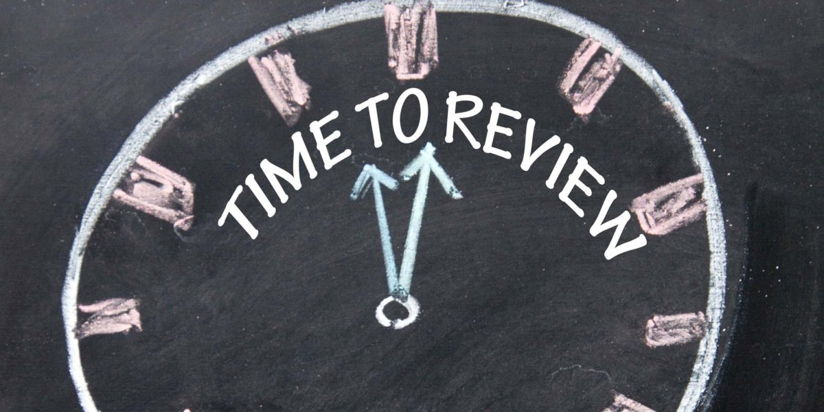 Chalkboard drawing of a clock with the words time to review written on the face.