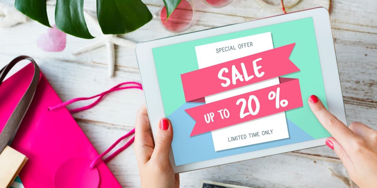 Woman holding a tablet with an ad for 20% off sale.